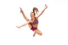 A menina do adolescente que faz os exercícios da ginástica isolados no fundo branco imagem de stock