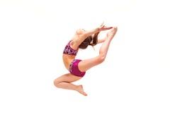 A menina do adolescente que faz os exercícios da ginástica isolados no fundo branco foto de stock royalty free