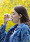 Menina do adolescente que usa o inalador da asma no parque Fotos de Stock