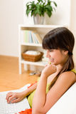 A menina do adolescente relaxa para casa - feliz com portátil Imagem de Stock Royalty Free