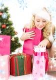 Menina do ajudante de Santa com presentes e árvore de Natal Fotos de Stock Royalty Free