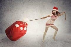 Menina do ajudante de Santa que puxa o saco pesado do Natal Fotografia de Stock