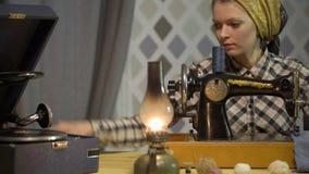 A menina do alfaiate costura o pano com a máquina de costura manual velha da mão A mulher retro da costureira trabalha em casa ou video estoque