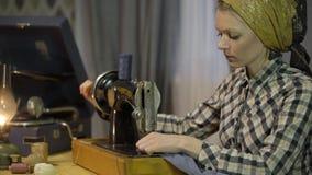 A menina do alfaiate costura o pano com a máquina de costura manual velha da mão A mulher retro da costureira trabalha em casa ou vídeos de arquivo