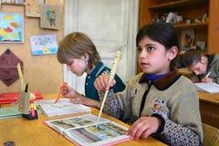 A menina do aluno de classes iniciais encontra a lição na escola rural Fotografia de Stock