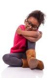 Menina do americano africano assentada no assoalho Imagem de Stock