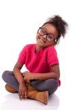 Menina do americano africano assentada no assoalho Fotografia de Stock