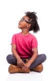 Menina do americano africano assentada no assoalho Fotografia de Stock Royalty Free
