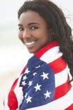 Menina do americano africano na bandeira americana na praia Foto de Stock Royalty Free