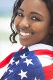 Menina do americano africano na bandeira americana na praia Fotos de Stock Royalty Free