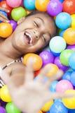 Menina do americano africano que joga em esferas coloridas Imagem de Stock Royalty Free