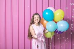 Menina do aniversário com balões e bolhas de sabão contra a parede cor-de-rosa do metal fotografia de stock royalty free