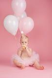 Menina do aniversário do bebê de um ano que come um queque foto de stock royalty free