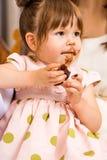 Menina do aniversário que come o bolo com crosta de gelo em sua cara imagem de stock