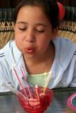 Menina do aniversário que funde para fora velas Foto de Stock
