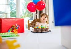 Menina do aniversário que olha presentes em casa Imagens de Stock Royalty Free