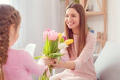 Menina do aniversário do ` s da mamã da mãe e da filha junto em casa que dá um grupo das tulipas imagens de stock