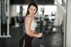 Menina do atleta no sportswear que d? certo e que treina seus bra?os e ombros com a m?quina do exerc?cio no gym foto de stock royalty free
