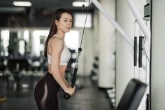 Menina do atleta no sportswear que d? certo e que treina seus bra?os e ombros com a m?quina do exerc?cio no gym imagem de stock royalty free