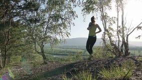 Menina do atleta que corre através das madeiras da floresta Povos reais, treinamento do esporte do corredor da mulher na mola ou  filme