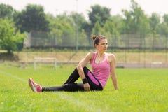 Menina do atleta que estica a grama lateral Foto de Stock Royalty Free