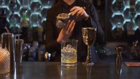 Menina do barman com suco de limão marrom longo do aperto do cabelo dentro de um cocktail com gelo em uma bacia de vidro e exclus video estoque