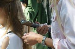 A menina do cabeleireiro enrola seu cabelo com um ferro Close-up imagem de stock