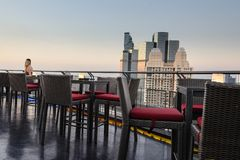 Menina do cabelo louro, hora de jantar crepuscular no terraço de um arranha-céus descoberto em Banguecoque, Tailândia foto de stock royalty free