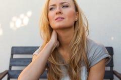 Menina do cabelo louro que senta-se atrás da tabela e que sofre porque o imagem de stock
