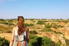 Menina do caminhante com trouxa e óculos de sol em sua cabeça que explora Portugal do sul Jovem mulher que caminha em Lagos, Port fotos de stock