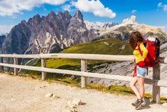 Menina do caminhante com a trouxa vermelha que descansa e que admira a vista em Parco Naturale Tre Cime, montanhas das dolomites, Fotografia de Stock