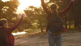 Menina do caminhante Duas meninas viajam, andam através da floresta e acenam suas mãos no monte As meninas viajam com trouxas em  vídeos de arquivo