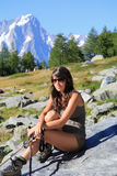A menina do caminhante senta-se em uma pedra da montanha Imagem de Stock