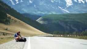 A menina do caroneiro está sentando-se perto da trouxa e da espera carros em uma estrada da montanha Há montanhas da neve no vídeos de arquivo