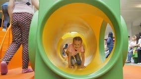 A menina do close up rasteja através das crianças escava um túnel no campo de jogos video estoque