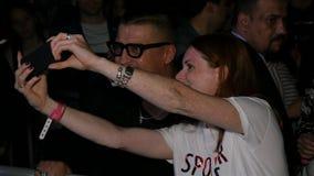 A menina do close up toma a foto com a estrela no concerto da noite video estoque