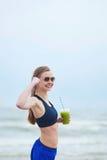 Menina do corredor que bebe o batido vegetal verde Fotos de Stock Royalty Free
