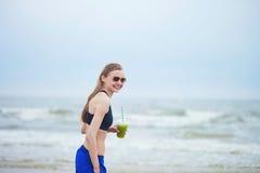 Menina do corredor que bebe o batido vegetal verde Fotografia de Stock
