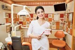 A menina do dentista das crianças no escritório do dentista mantém a escova de dentes de Manika e uma escova de dentes foto de stock royalty free