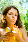 A menina do divertimento come o hot-dog na natureza Foto de Stock
