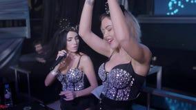 Menina do DJ na dança da parte superior do fulgor na plataforma giratória A menina de MC canta nas orelhas de rato nightclub video estoque