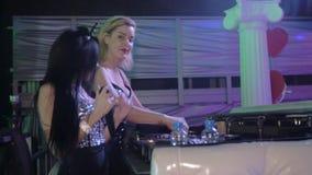Menina do DJ no giro superior do fulgor na plataforma giratória Dança da menina de MC no bodysuit 'sexy' clube filme