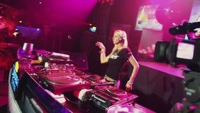Menina do DJ que gira e que dança na plataforma giratória no partido no clube noturno spotlights filme