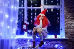 Menina do duende do Natal na janela Foto de Stock Royalty Free