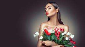Menina do encanto da beleza com as flores da tulipa da mola Jovem mulher bonita com um grupo de flores coloridas da tulipa fotografia de stock