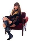Menina do encanto da forma que senta-se na cadeira macia. Imagens de Stock Royalty Free
