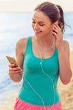 Menina do esporte com o dispositivo na praia Imagens de Stock