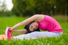 Menina do esporte da aptidão no sportswear que faz o exercício da aptidão da ioga exterior Imagens de Stock Royalty Free