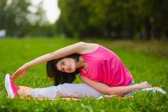 Menina do esporte da aptidão no sportswear que faz o exercício da aptidão da ioga exterior Fotografia de Stock Royalty Free