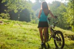Menina do esporte na tabuleta digital da posse da bicicleta Imagem de Stock Royalty Free